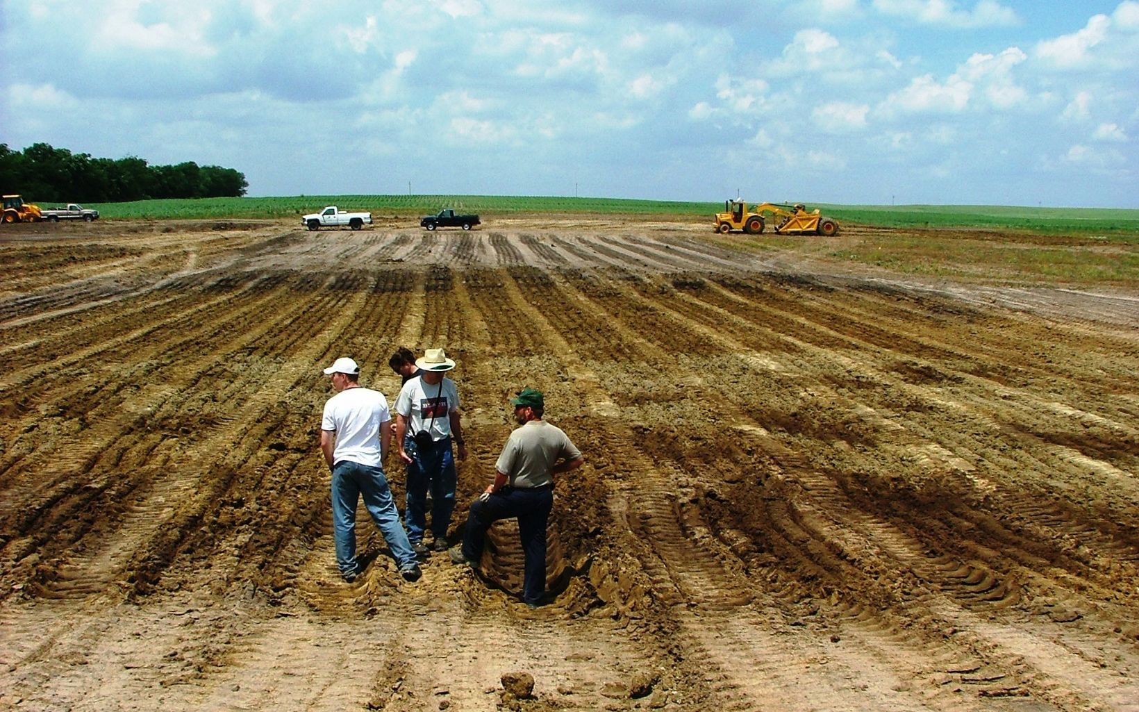 Farmers survey soil in field