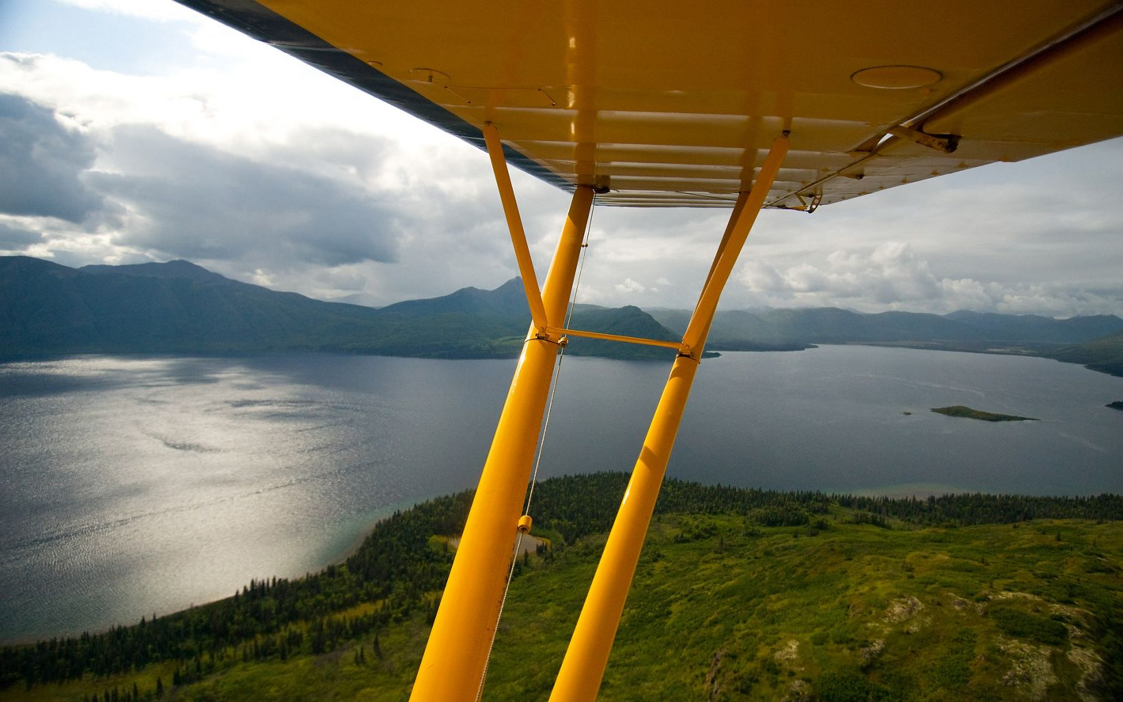 Aerial view of Alaska's Bristol Bay headwaters from the backseat of a yellow Piper Super Cub.