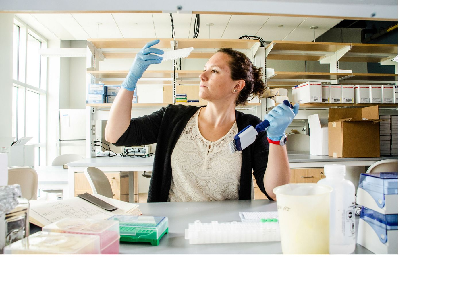 Intern sits in lab, surrounded by lab equipment, holds container up to light from nearby window