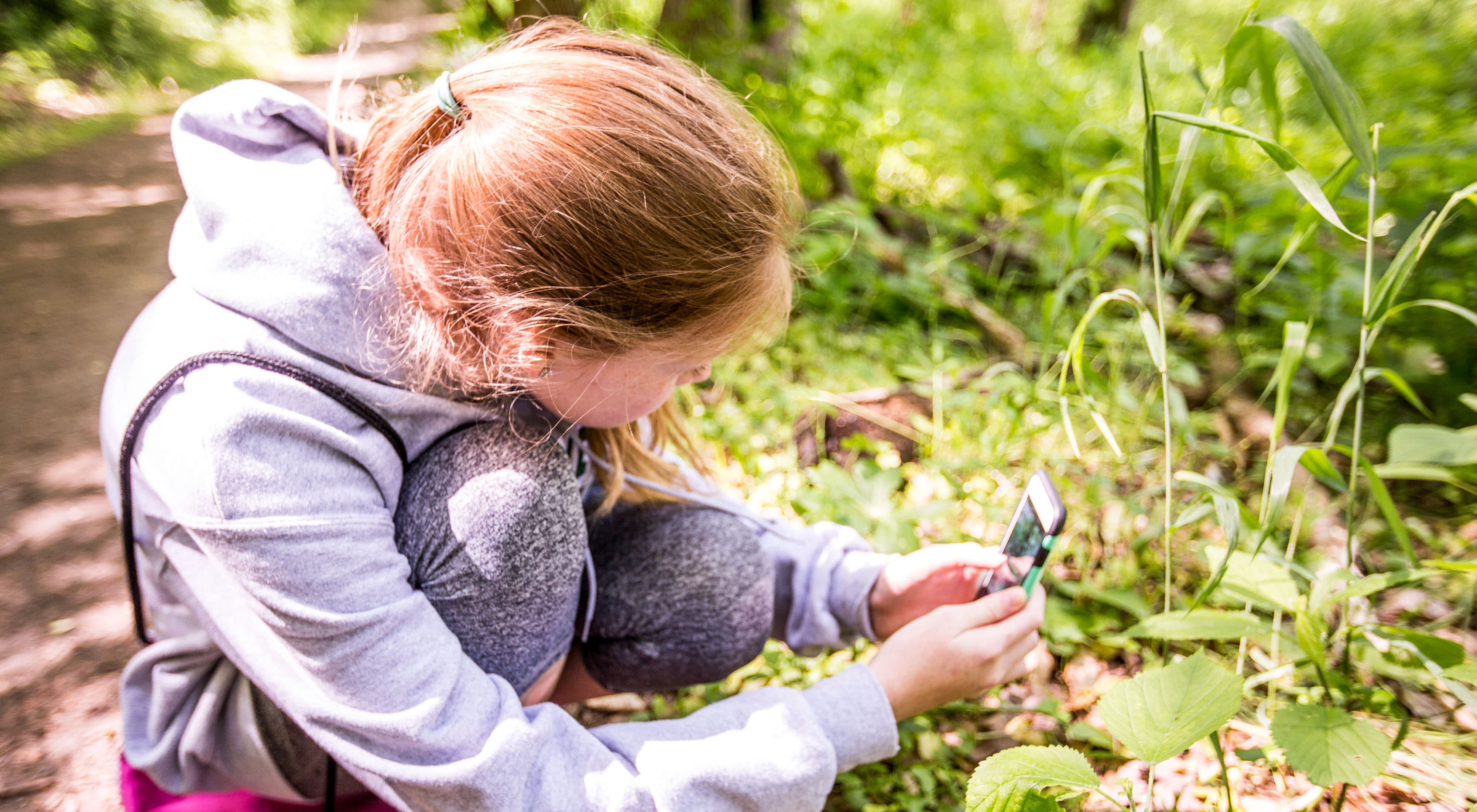 young girl taking photo of plants