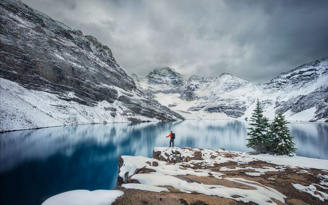 Lone hiker along snowy mountain lake