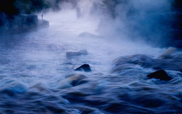 """Fly fishing in early morning mist near the famous rafting spot called """"crib works"""", on the East Branch of the Penobsot River just upriver of Mount Katahdin in Maine."""