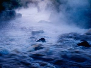A long exposure of a misty river flowing over rocks