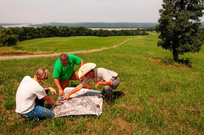 Three people in a field look over a map.