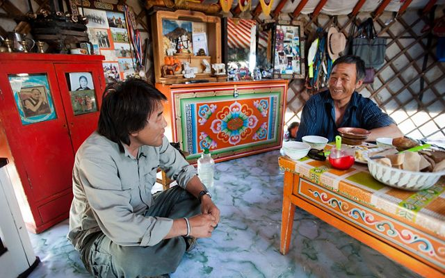 two men sit on the floor around a table in a yurt