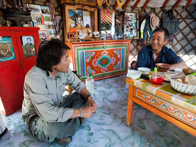 The Nature Conservancy's Galbadrakh (Gala) Davaa, (on left) Director of Conservation for the Mongolia Program with Otgonbaatar Tsog, a Mongolian herder and Conservancy partner in Mongolia, talking in Tsog's ger (ger, or yurt, is the traditional tent like home of nomadic Mongolian herders), in Mongolia. The rich natural resources of Mongolia's steppes are attracting increased development, which is threatening the balance between humans and wildlife that has defined this country's past. Through traditional land protection and cutting edge initiatives like Development by Design, the Conservancy is working to create a sustainable future that honors and preserves the sustainable culture of Mongolia's grasslands.
