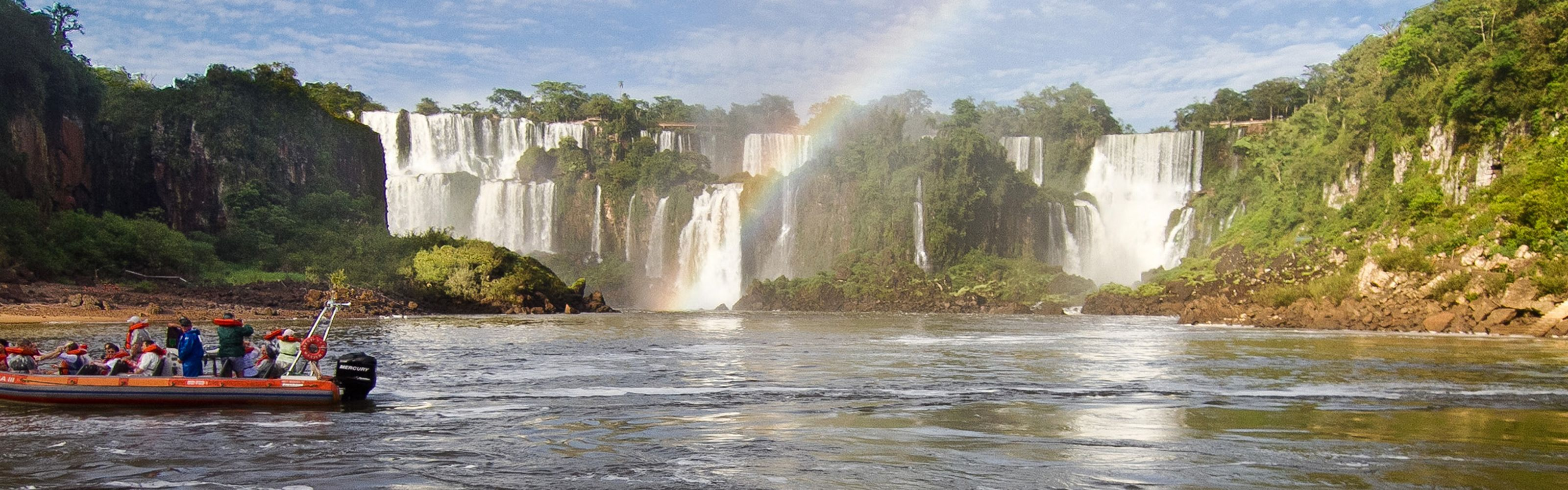 Tourists sit in a red motor boat at the based of Iguaçu