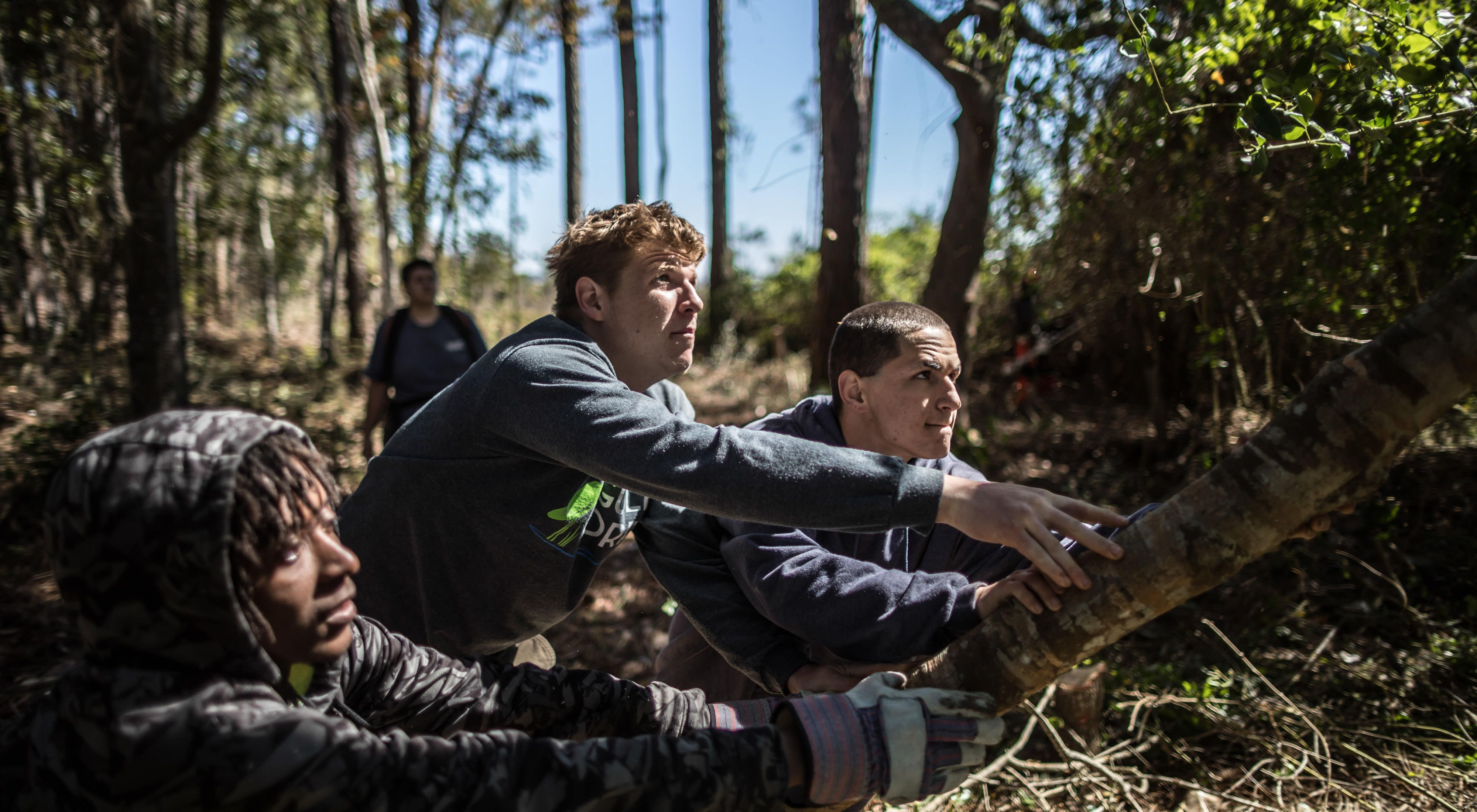 Conservation Corps members Quantavius Fuller, 20, Destin Dodd, 20, and Jonathan James, 18, push down a cut tree in Apalachicola, Florida, while working on environmental sustainability needs for the Panhandle region of the state. This project is also supported by The Nature Conservancy.