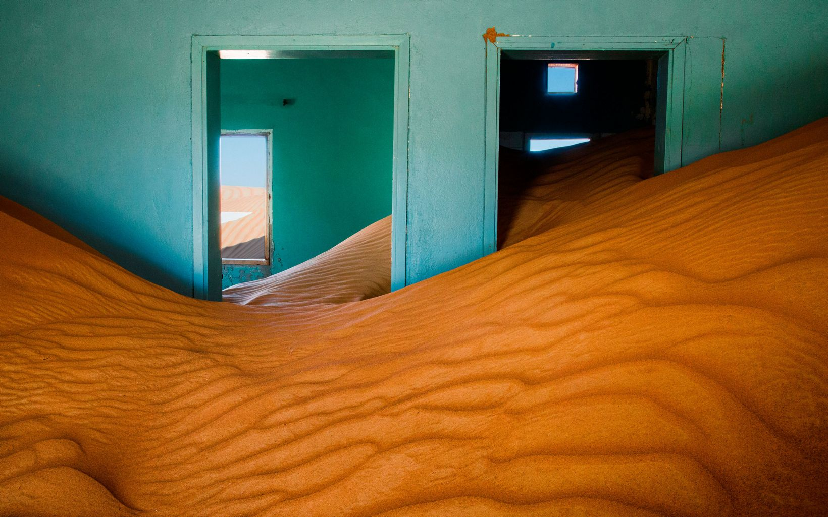 Abandoned home filled with sand in the Arabian Desert, United Arab Emirates.