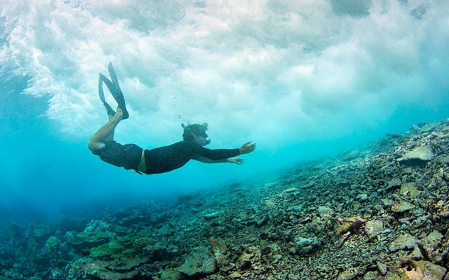 Diver under a breaking wave at the reef crest near Pengiun Spit withing Palmyra Atoll in the equatorial Northern Pacific.
