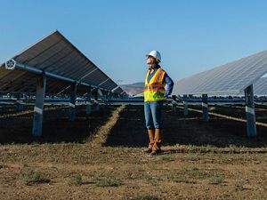 A woman stands on the ground in between two solar arrays wearing a reflective orange vest and a construction hard hat, looking to the upper lefthand side of the screen.