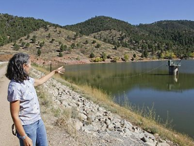 Laura McCarthy points to area adjoining Nichols Reservoir (second hillside from left) where management practices have reduced forest density to fire-safe levels.