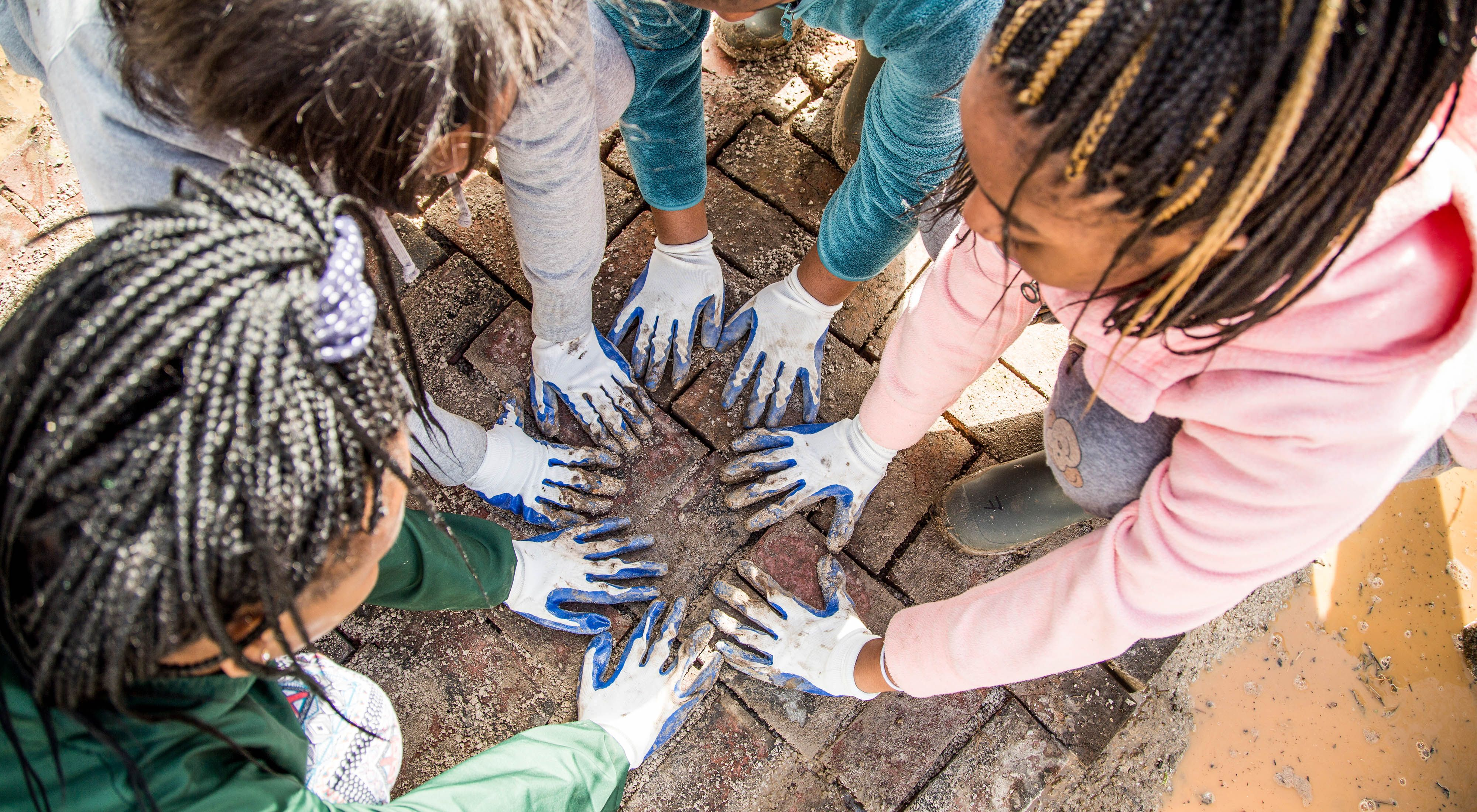 An above-down image of young girls with their hands, adorned in muddy work gloves, together in a circle.