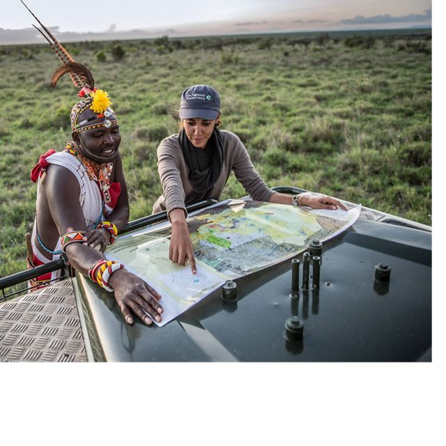 Ecotourism guide Sam Brown and TNC Project Officer Chantal Migongo-Bake review a map of Loisaba Conservancy in northern Kenya.