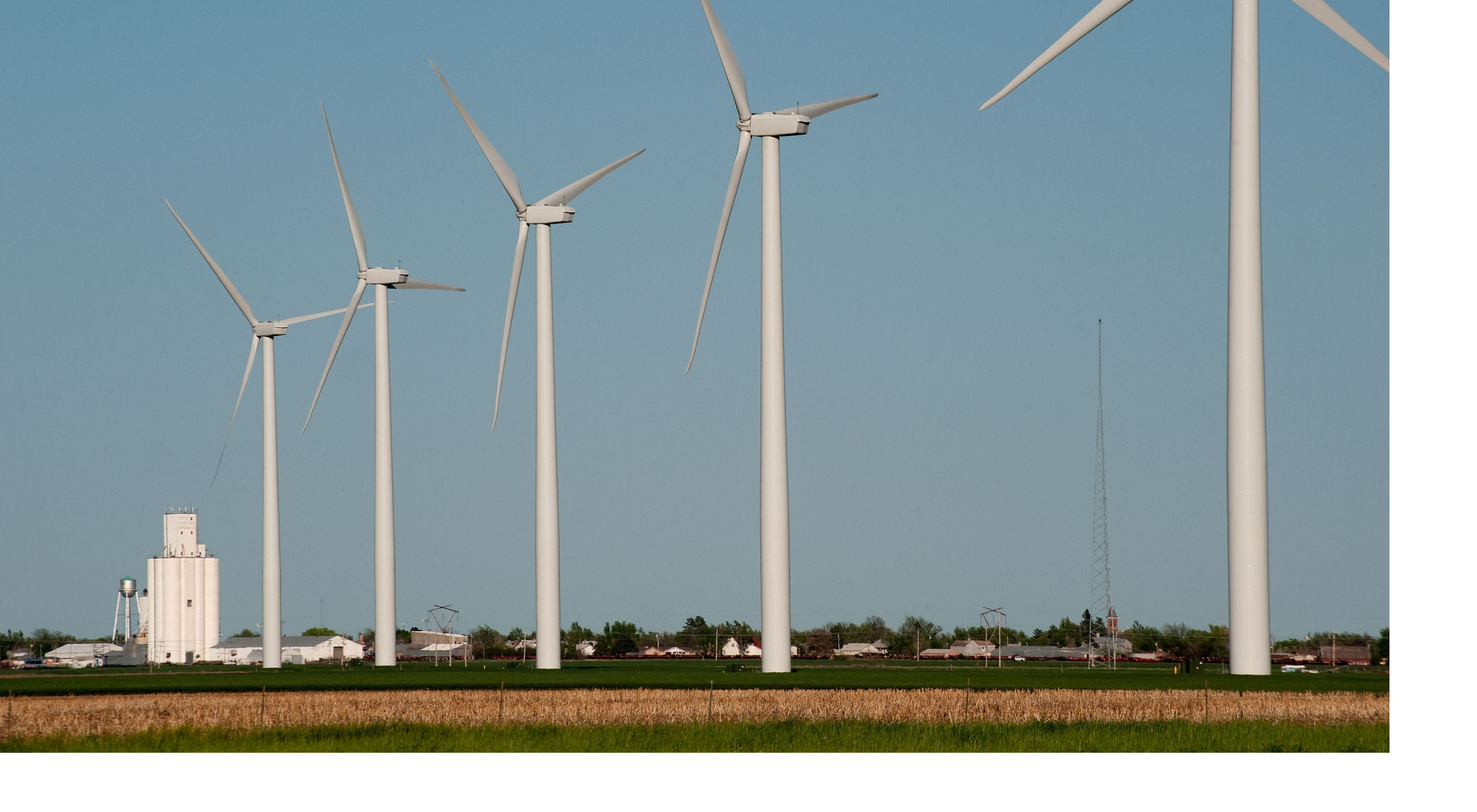 Eight industrial wind turbines over crops on a Kansas farm.