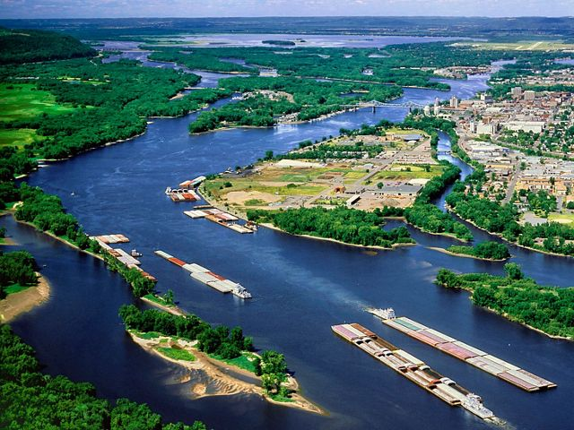 An aerial view of barges on the Mississippi river as it curves around populated and forested areas.