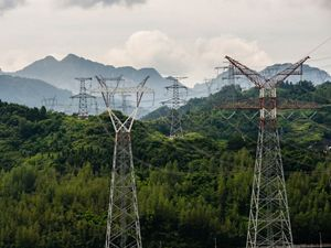 View of high voltage power lines on a mountain range.