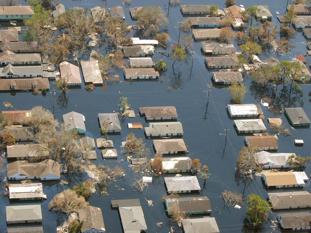 An aerial view of a severely flooded New Orleans neighborhood with floodwater reaching roofs.