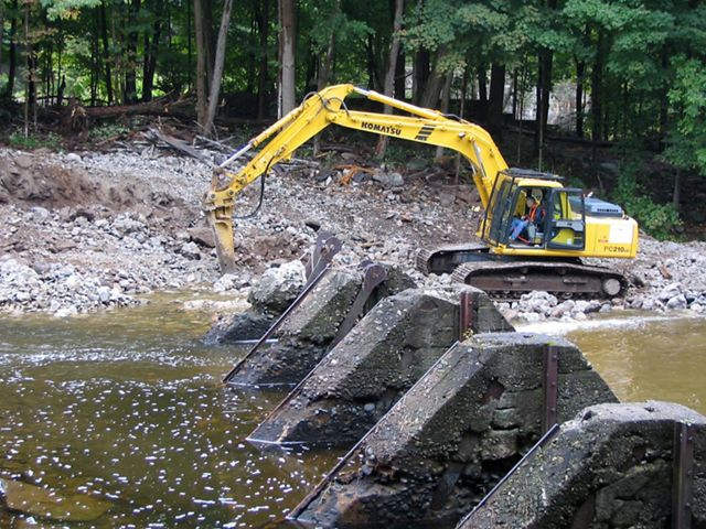 Construction equipment removing a dam.