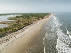 Aerial view of Hog Island, a narrow expanse of sand backed by green scrub and fronted by gently lapping waves.
