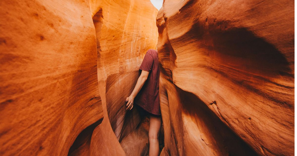 Woman squeezes through a narrow slot canyon in Escalante National Monument in Utah.