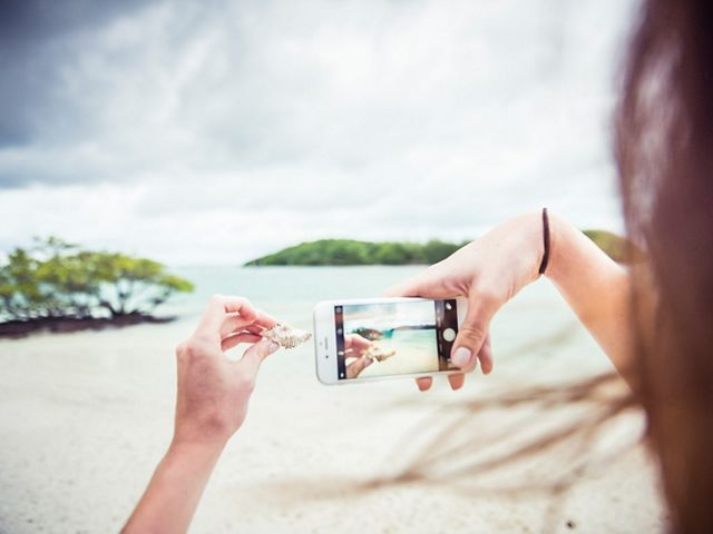 woman uses iPhone to photograph hermit crab shell on a beach
