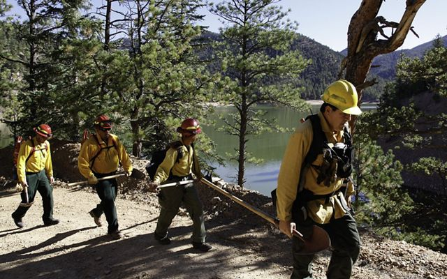 Wildland fire workers hike with hand tools along a mountain road in New Mexico.