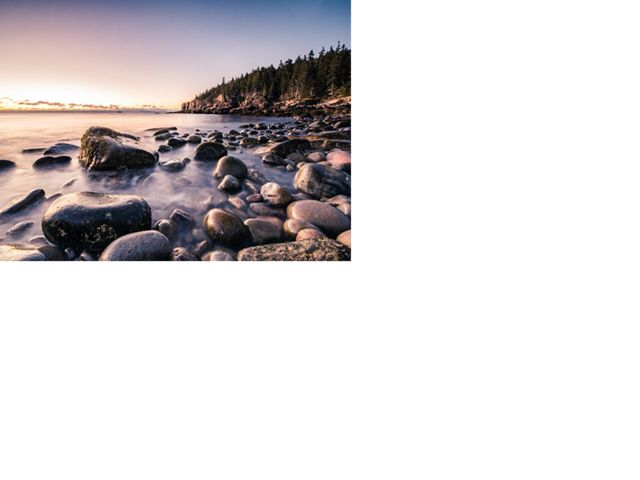 The first light of dawn touches Cobblestone Beach in Acadia National Park, Maine.