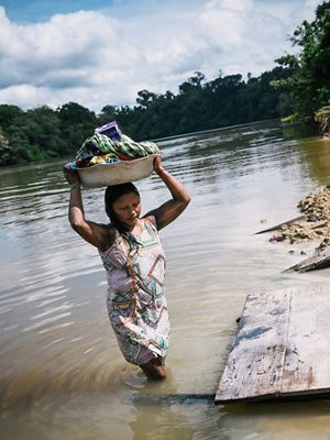 A Xikrin woman in the Pot-Kro Village carries items washed in the river.