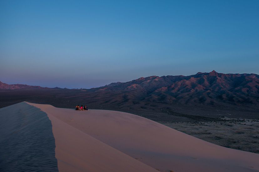 Photo at dusk of California dunes, three people in background sitting on dune.