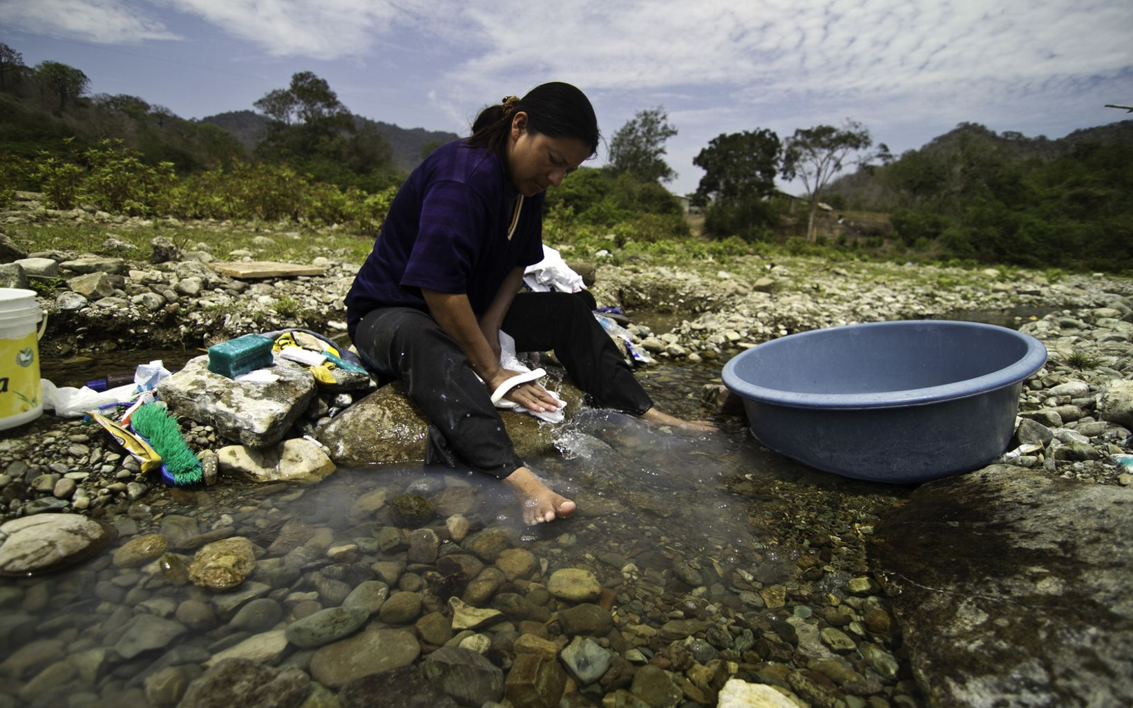 A woman washes clothes in the Ayampe River in Ecuador's Manabí Province. The Ayampe River has many responsibilities beyond its ecological role. It also supports the life of the communities within its watershed. The Conservancy is working with local partners to develop a water fund to help protect this water source.