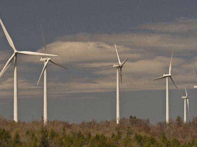 six wind turbines against blue sky backdrop