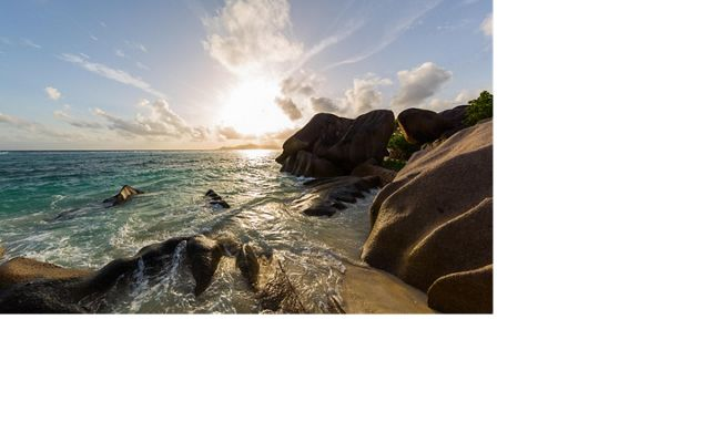 Worn granite rocks in the surf and sand define the coastlines of Seychelles's inner islands.