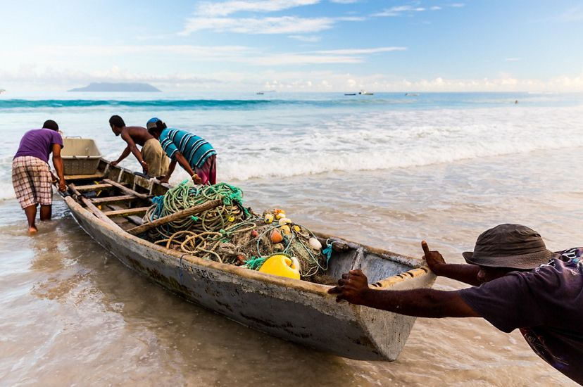 A group of fishers pushing a boat into the ocean