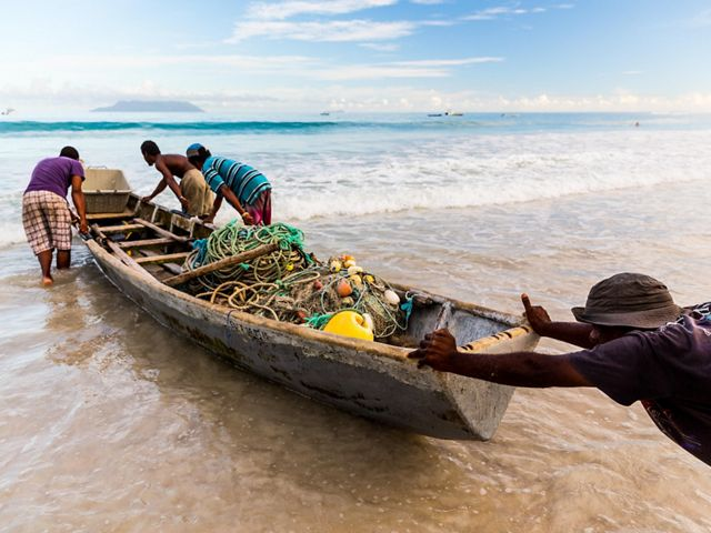 men pushing a small boat into the sea