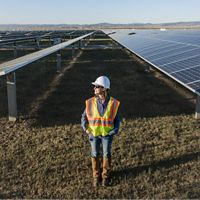 A woman stands in between rows of solar panels.