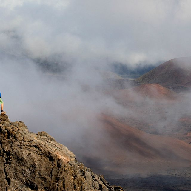A hiker stands on a rocky peak looking across a cloudy valley.