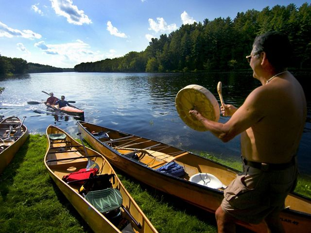 "A participant in the ""Katahdin 100"", beats a drum greeting to canoes on the Penobscot River in Maine. The annual Penobscot Tribe spiritual journey by canoe, kayak, war canoe and some on foot, from Indian Island up the Penobscot River 100 miles to the base of Mount Katahdin. An unprecedented array of partners, including the Conservancy and the Penobscot Indian Nation, have come together to accomplish the goal of restoring the Penobscot River."