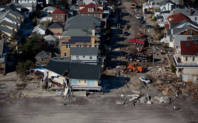 Aerial view of destruction caused by Hurricane Sandy. Rows of houses facing a beach show varying degrees of damage. In the foreground a yellow house is split in two.