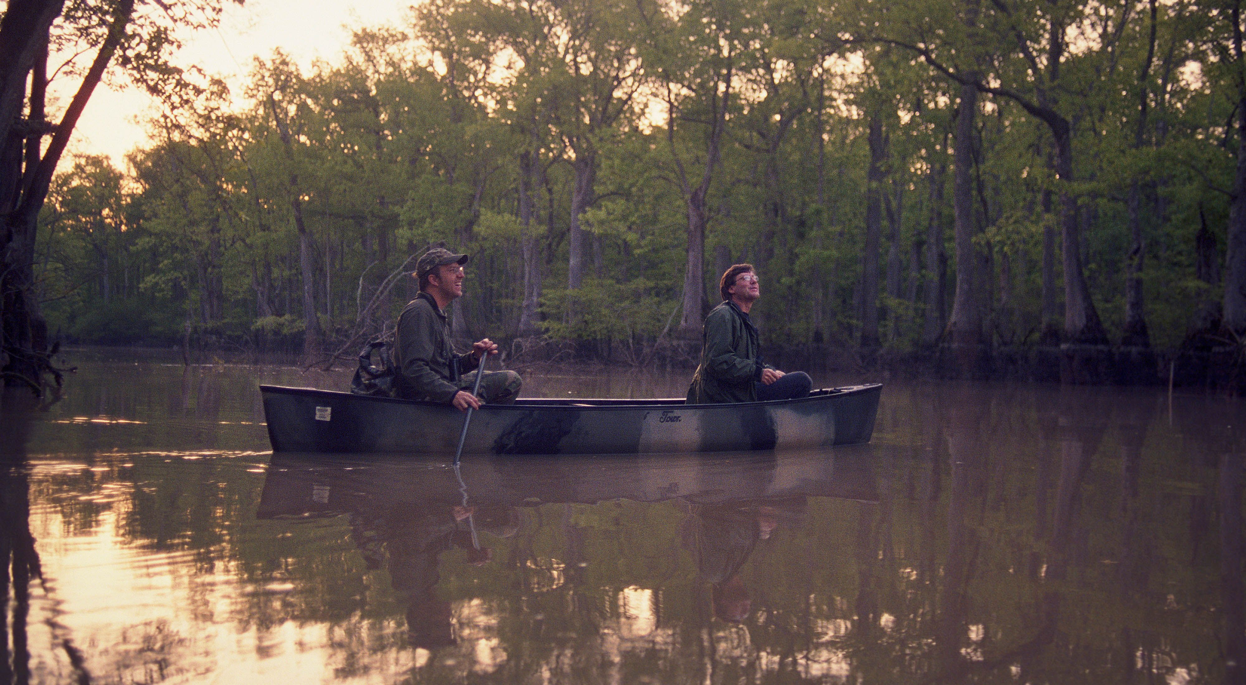 World-renowned bird expert David Sibley, in front of the canoe with researcher Elliott Swarthout search the Big Woods of Arkansas for the elusive Ivory-billed Woodpecker during the Spring of 2005.
