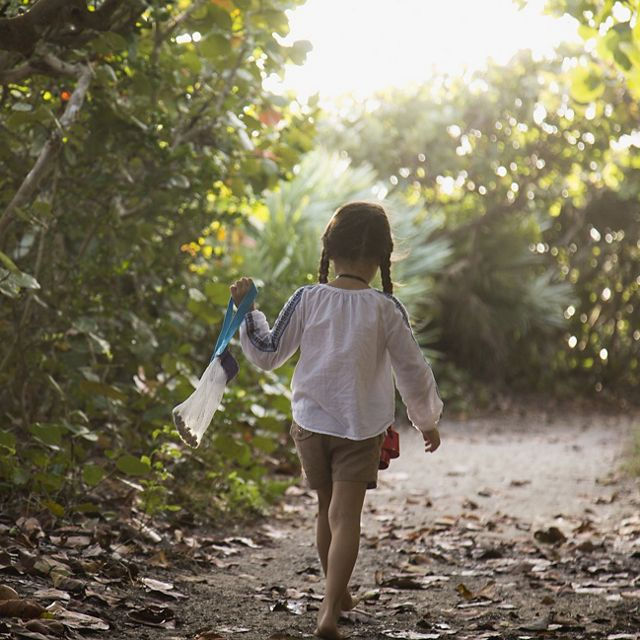 Young girl waking along a wooded path.