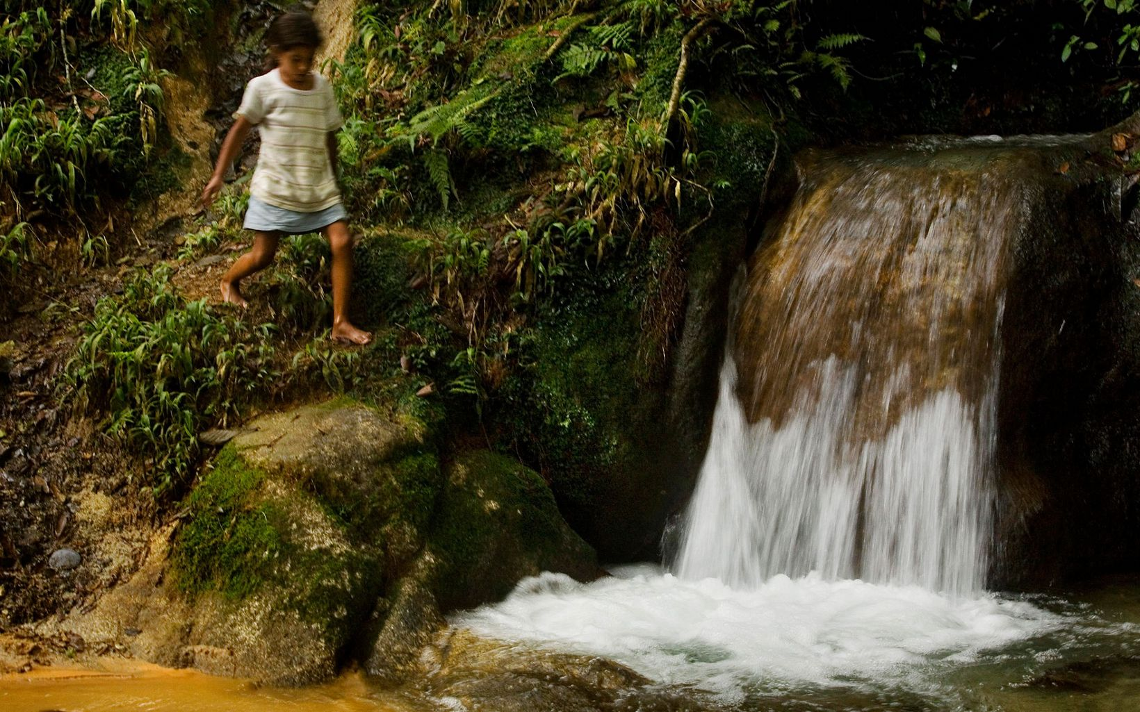 A girl plays by a clean waterfall near Los Dajaos, where environmental education has taught residents how to prevent water pollution.