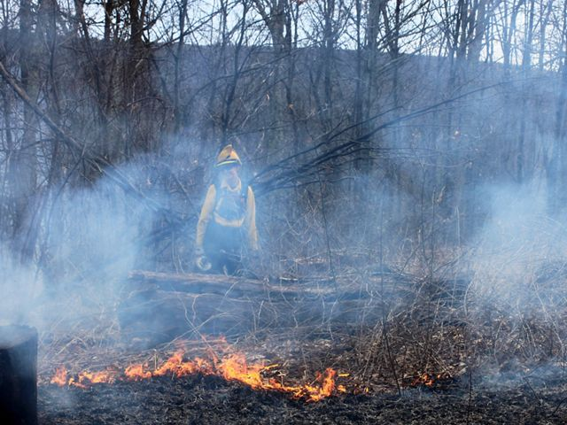 A women wearing yellow fire retardant gear monitors a small fire during a controlled burn. Smoke rises around her almost obscuring her from view.