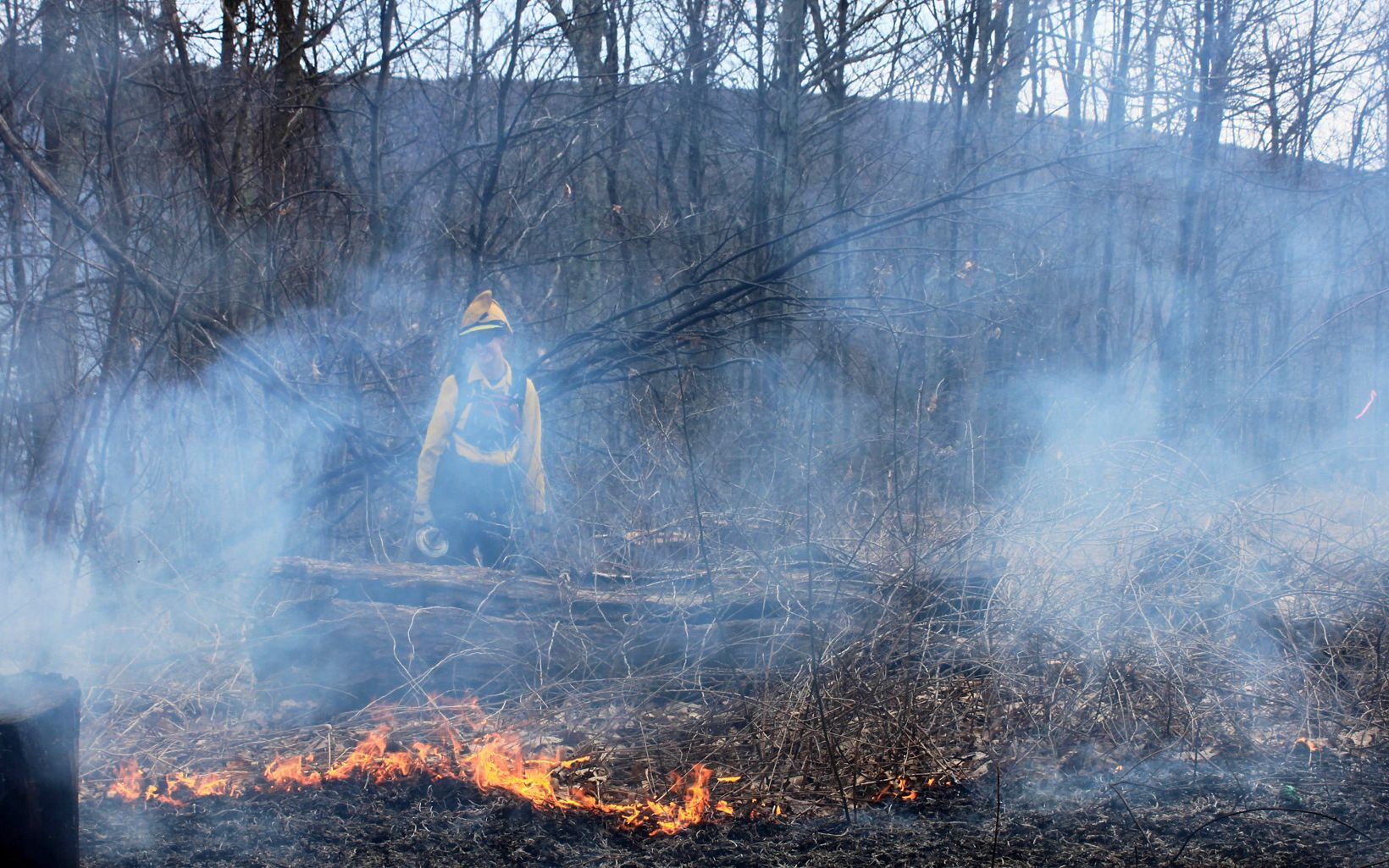 A woman wearing yellow protective fire gear and a yellow helmet stands to a small fire as it burns through the leafy vegetation on the ground. She is envolved in white smoke.