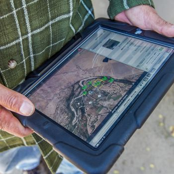 Gary Jordan, of Keller-Bliesner Engineering, uses a tablet to identify potential restoration sites along the San Juan River near Shiprock, New Mexico.