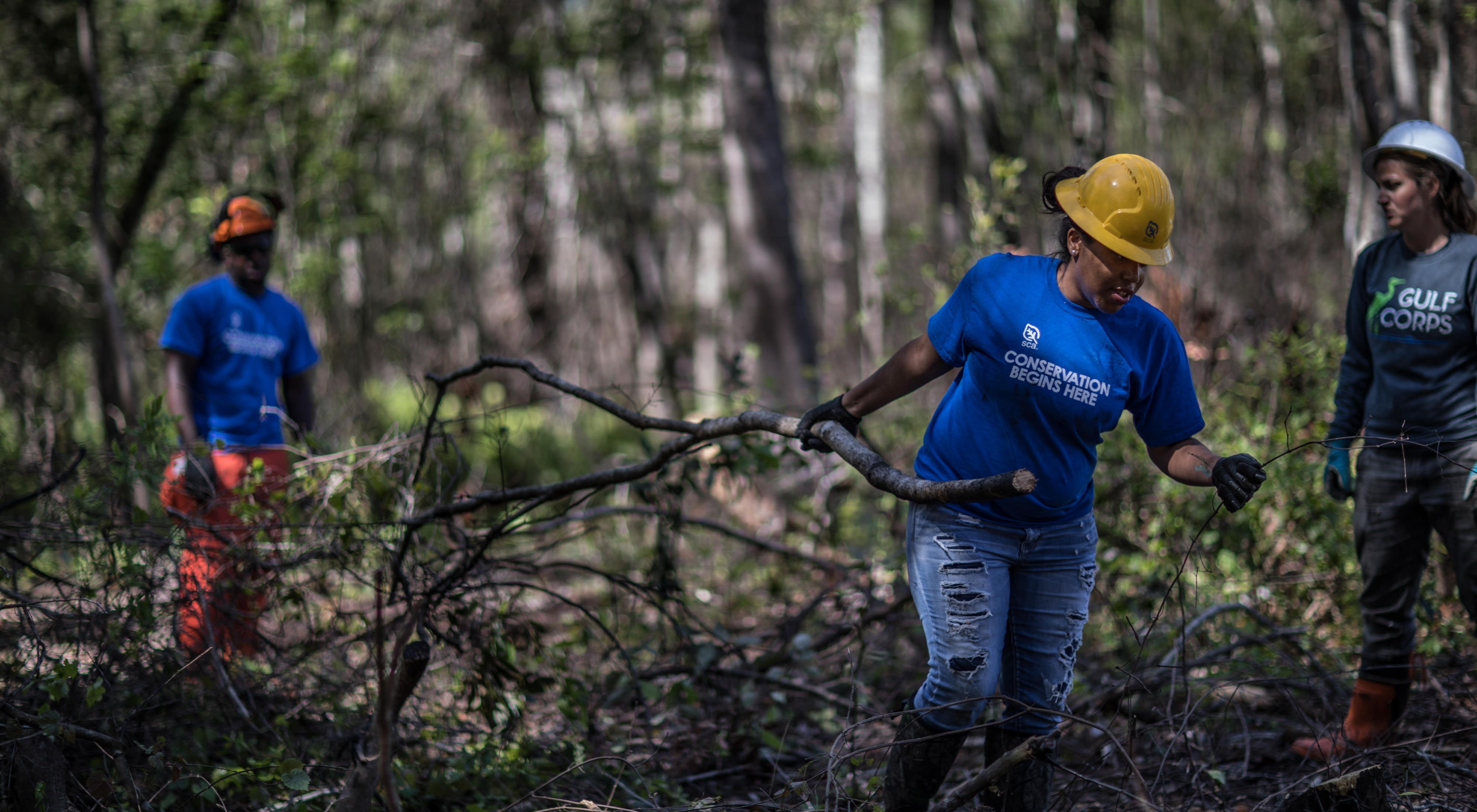 Three young people in hard hats, gloves and conservation corps shirts, clearing branches in a forest.