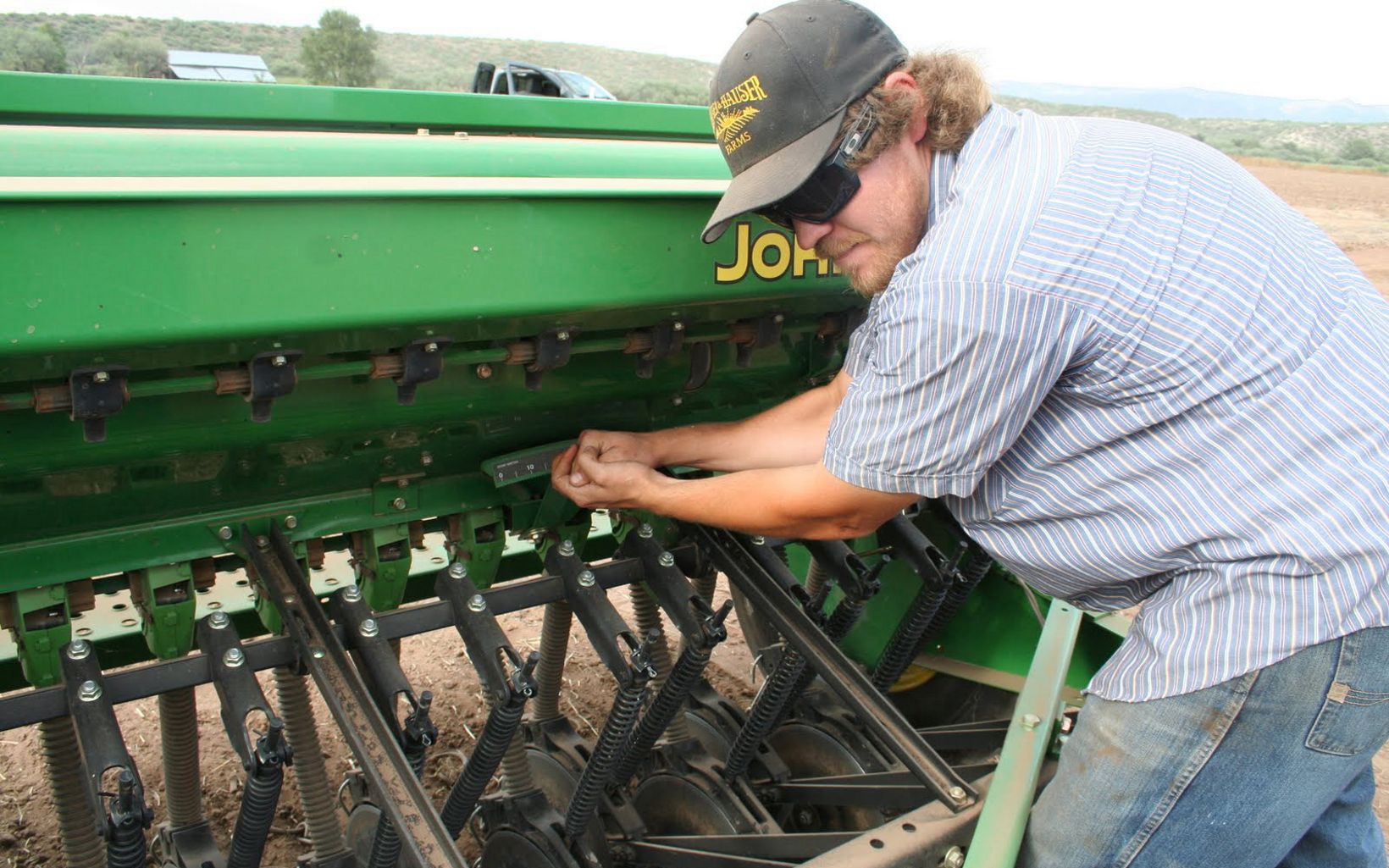 Zach Hauser checks the seeder while planting native grass seed on a field at the Conservancy's Shield Ranch on the Verde River, Arizona.