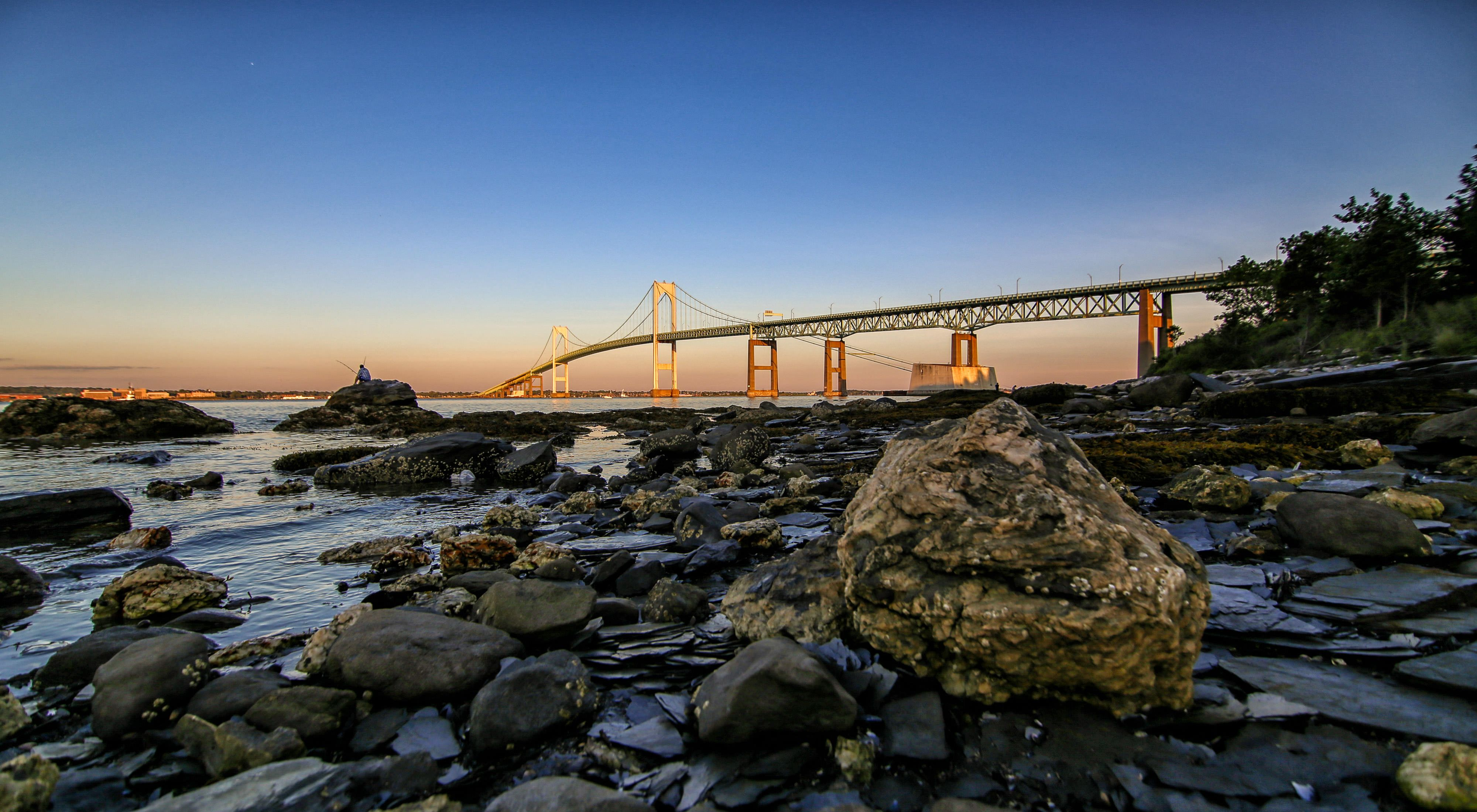 Photo of the bridge at Newport, Rhode Island, at sunrise, with rocks and tidal waters in foreground.
