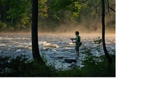 A man fishing on the Kennebec River in Maine.