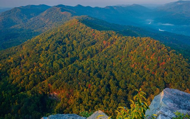 Fall colors of red and orange begin to show on a green forested mountain ridge.